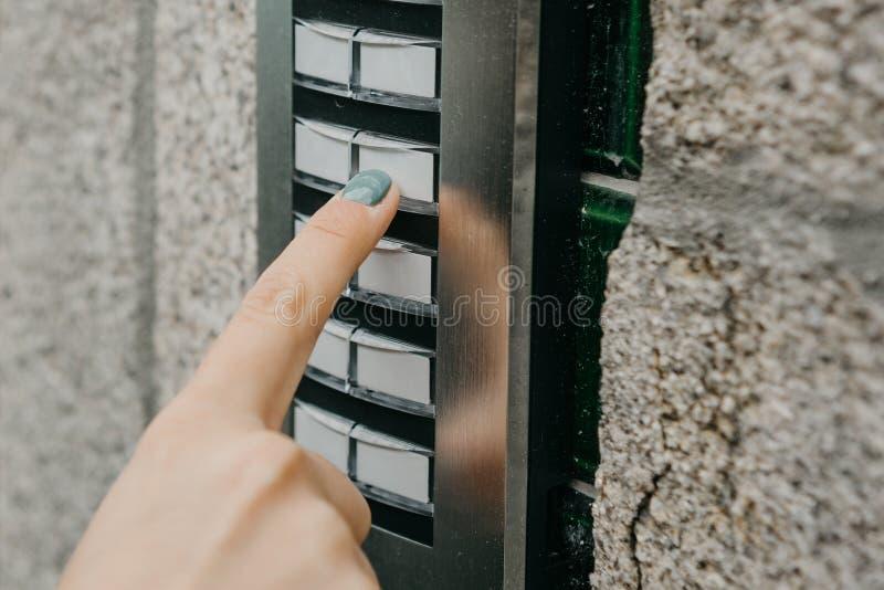 Девушка нажимает кнопку doorphone или вызывает внутренную связь стоковые изображения