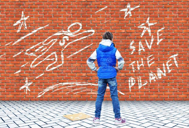 Девушка нарисовала с мелом на кирпичной стене чертеж с спасением звонка планета стоковое изображение rf