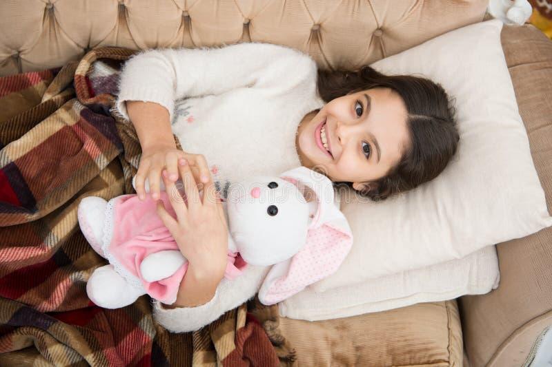 Девушка наслаждается выровнять время с любимой игрушкой Кровать положения ребенк и подушка кресла игрушки зайчика объятия укрываю стоковое изображение rf