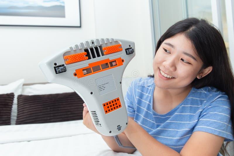 Девушка наслаждается использовать пылесос лепты используя тюфяк кровати чистки стоковое изображение