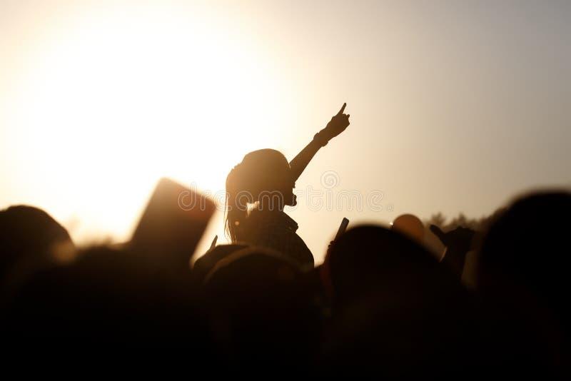 Девушка наслаждаясь концертом, имеющ потеху на плечах друга стоковые фото
