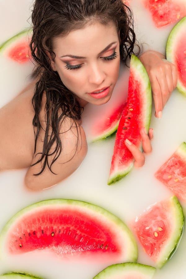 Девушка наслаждается ванной с молоком и арбузом. стоковая фотография rf