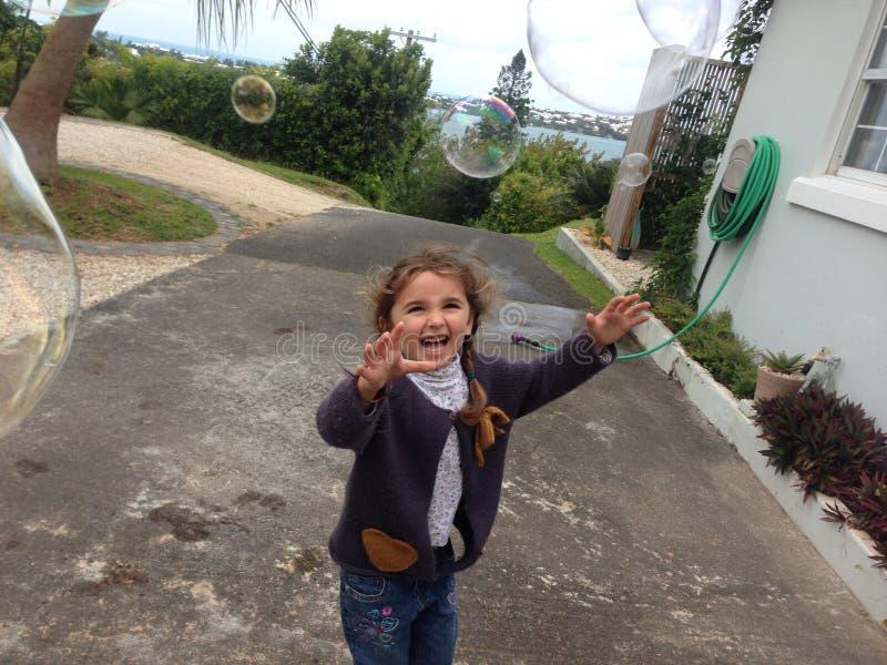 Девушка наслаждаясь хлопать пузыря стоковая фотография