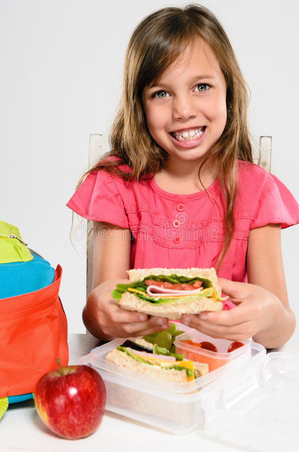 Девушка начальной школы около для еды ее упакованного обеда стоковое фото