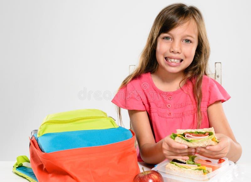 Девушка начальной школы около для еды ее упакованного обеда стоковое изображение rf