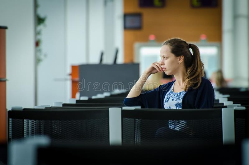 Девушка на авиапорте ждет полет стоковое фото rf