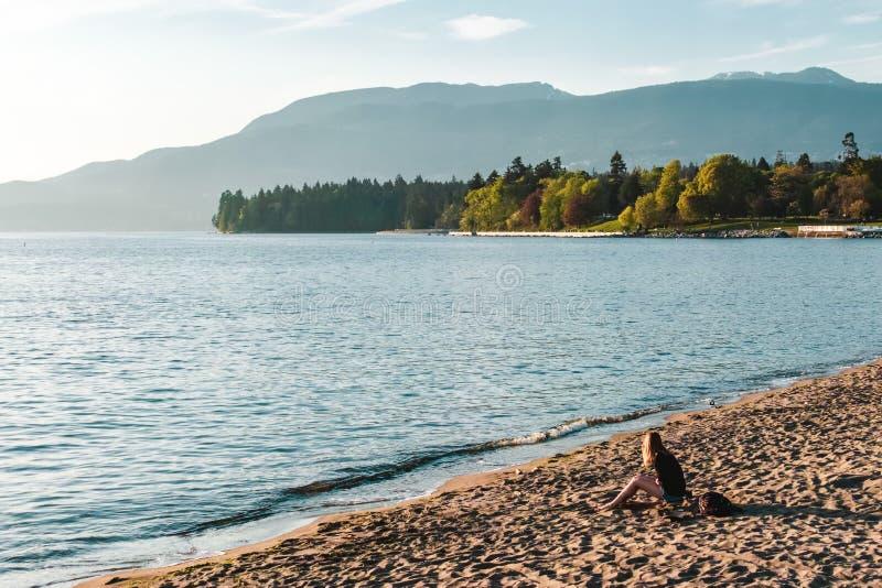 Девушка на английском пляже залива в Ванкувере, ДО РОЖДЕСТВА ХРИСТОВА, Канада стоковые фото