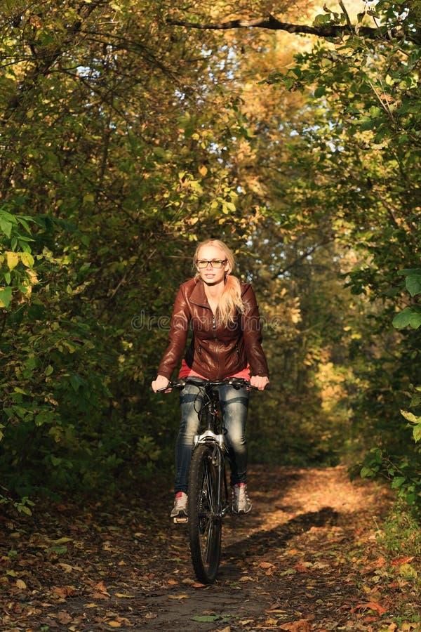 Девушка на велосипеде в пуще стоковая фотография
