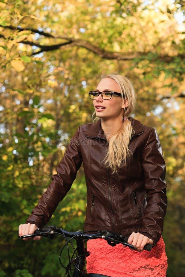 Девушка на велосипеде в пуще стоковая фотография rf