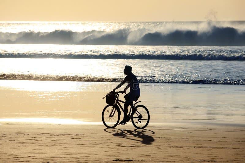 Девушка на велосипеде едет вдоль океана на заходе солнца стоковые фото