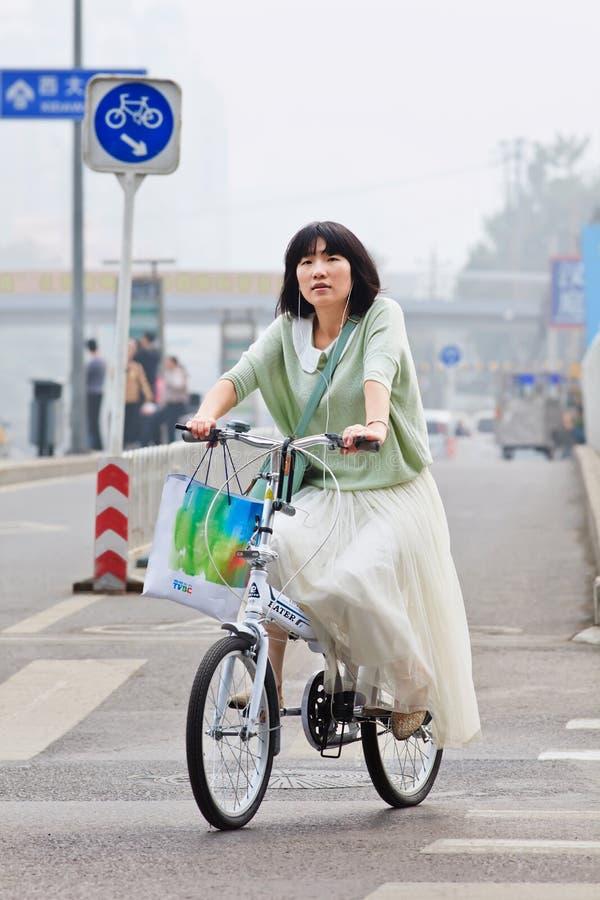 Девушка на велосипеде складчатости в смоге укрывала Пекин, Китай стоковое изображение