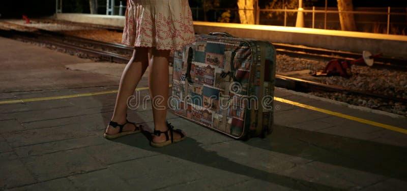 Девушка на вокзале с чемоданом во время ночи стоковые изображения
