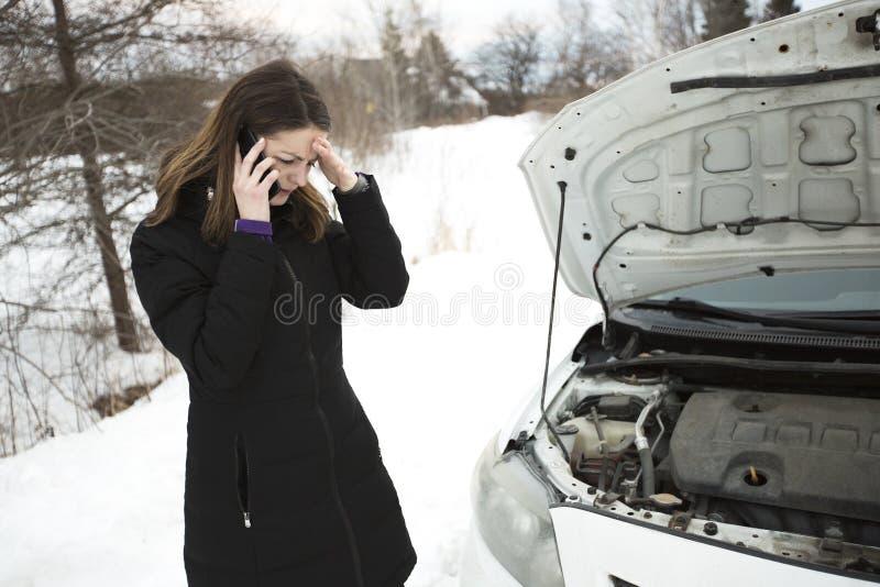 Девушка на дороге зимы вызывает телефон около автомобиля стоковые фотографии rf