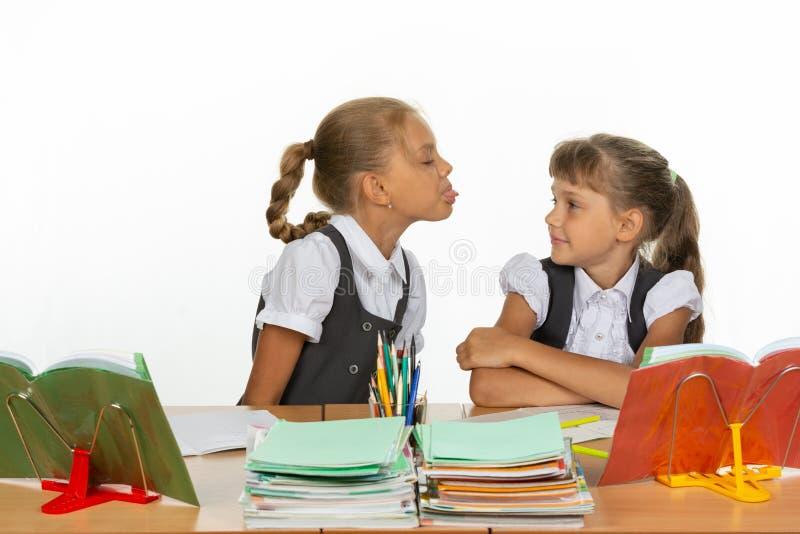 Девушка на ее столе показала язык к другой девушке стоковое изображение rf