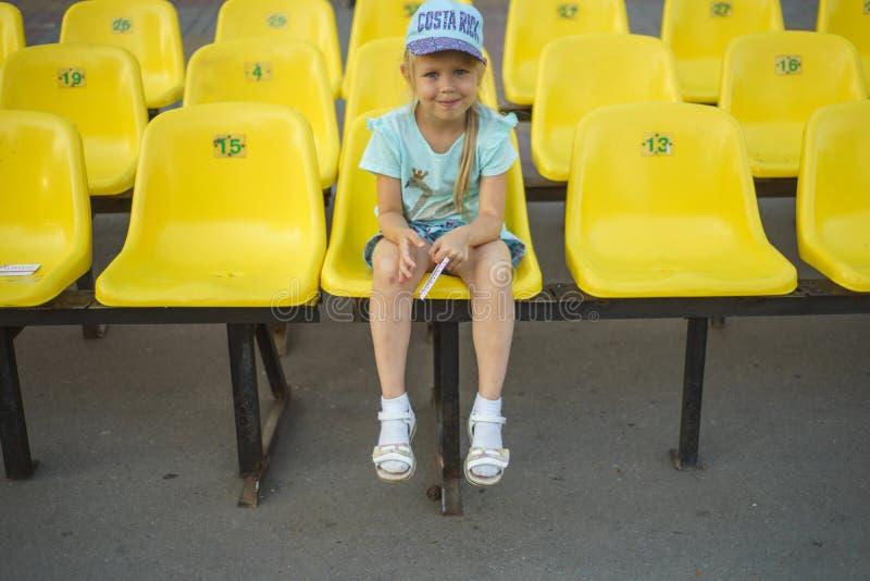 Девушка на желтых местах стадиона стоковое фото