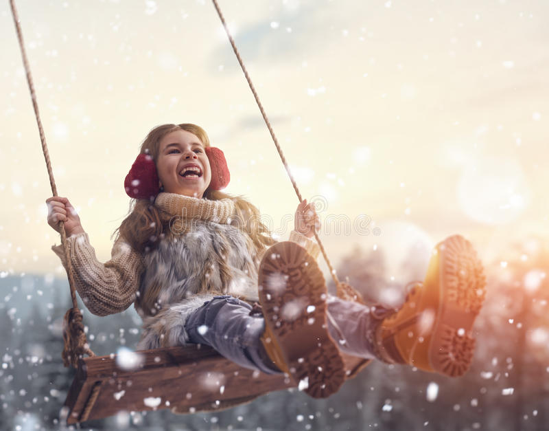 Девушка на качании в зиме захода солнца стоковое фото
