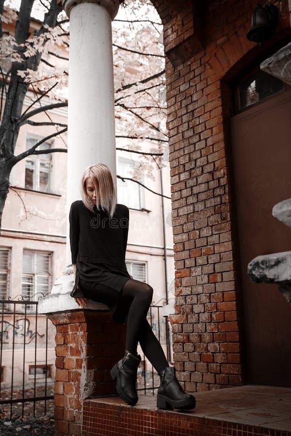 Девушка на кирпичной стене в черном платье стоковые фото