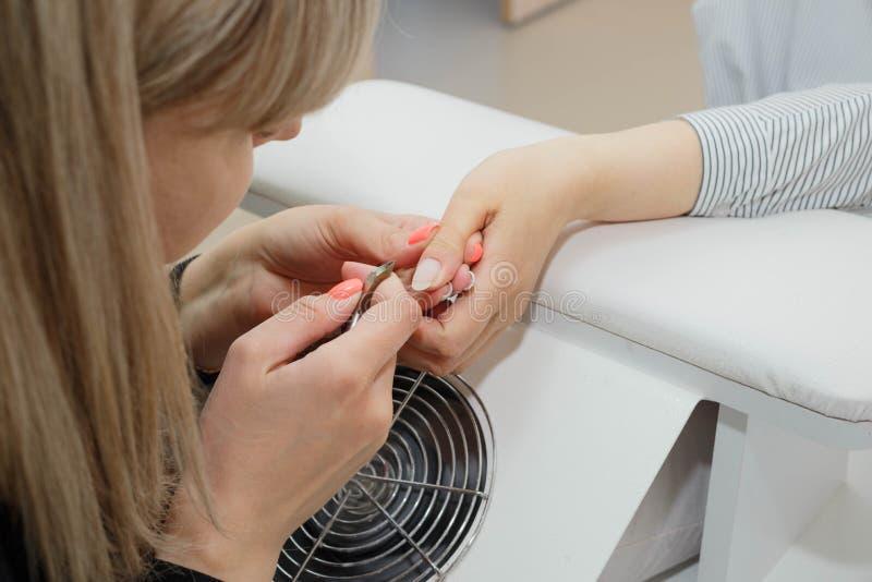 Девушка на мастере обслуживания ногтя стоковые фотографии rf