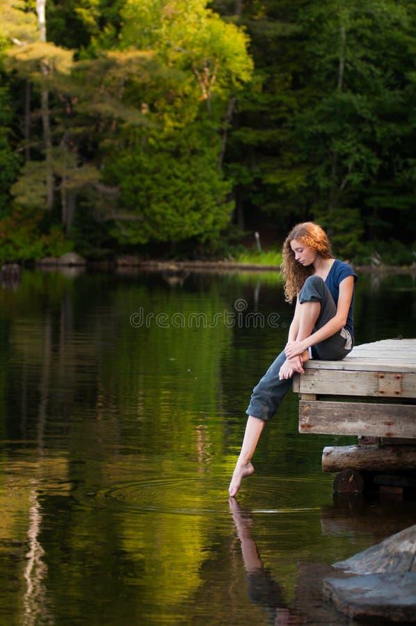 Девушка на доке берега озера стоковое изображение rf