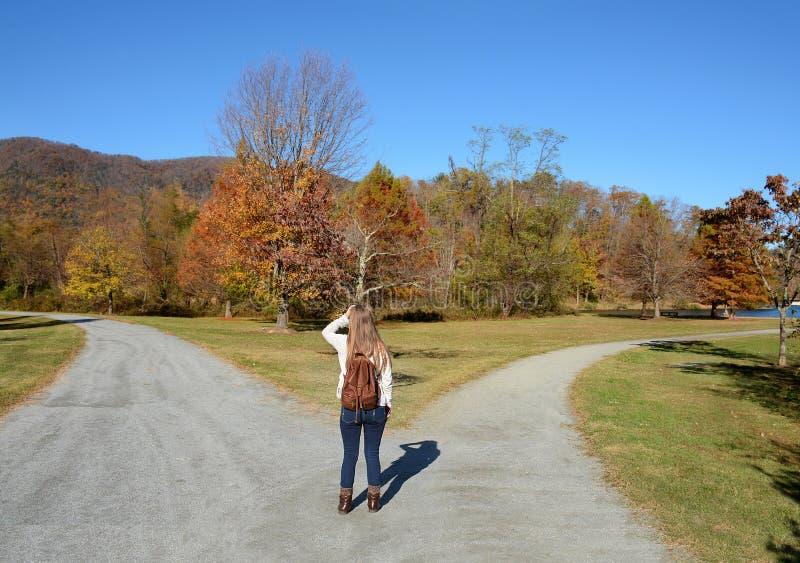 Девушка на разветвленной дороге делая решение стоковое изображение