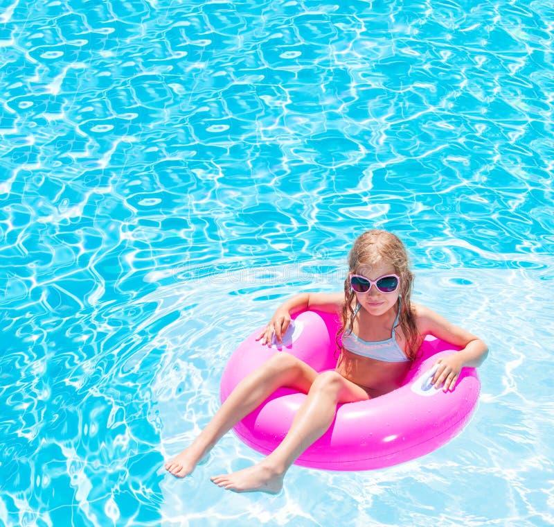 Девушка на раздувном кольце в бассейне стоковые фотографии rf