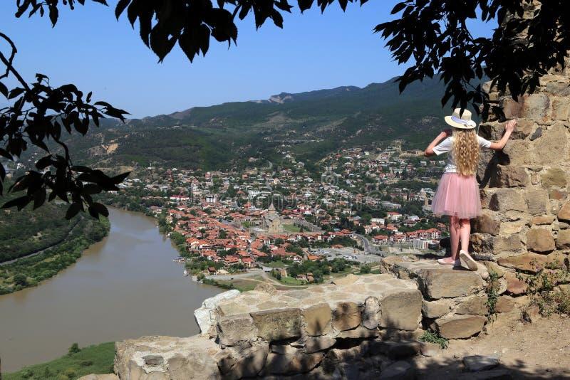 Девушка на руинах стены старого грузинского правоверного монастыря Jvari на предпосылке стечения  стоковое изображение