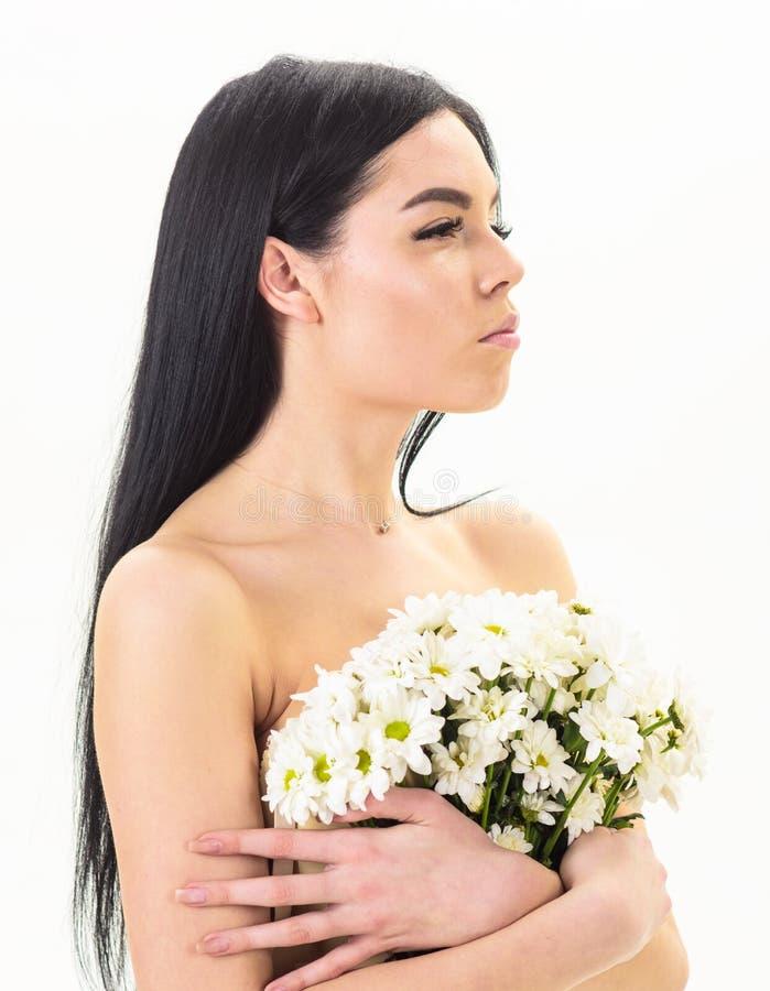 Девушка на спокойной стороне стоит нагой и держит цветки стоцвета перед концепцией здоровья кожи комода Дама покрывает груди стоковые фотографии rf