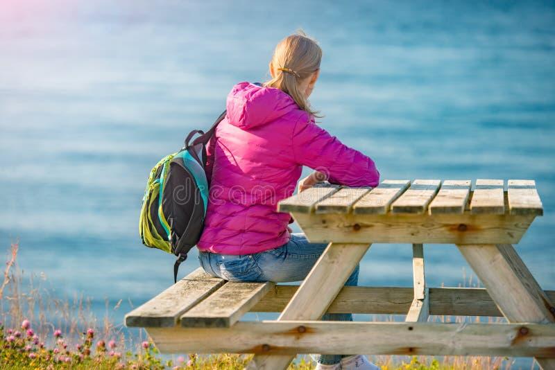 Девушка на таблице стенда на береге в Норвегии, Европе стоковые изображения