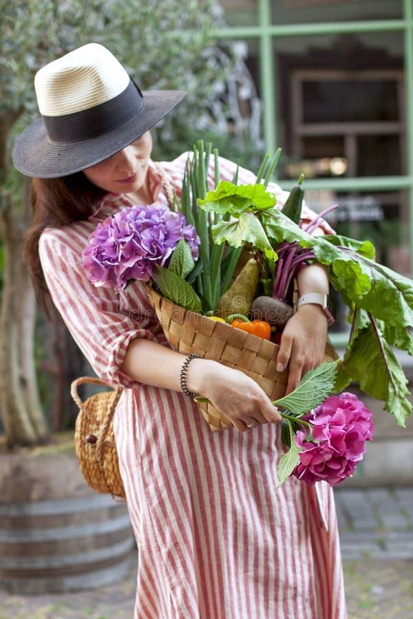 Девушка на улице города с большой корзиной овощей и цветков в ее руках красивейшая женщина покупк Идти вперед стоковое фото rf