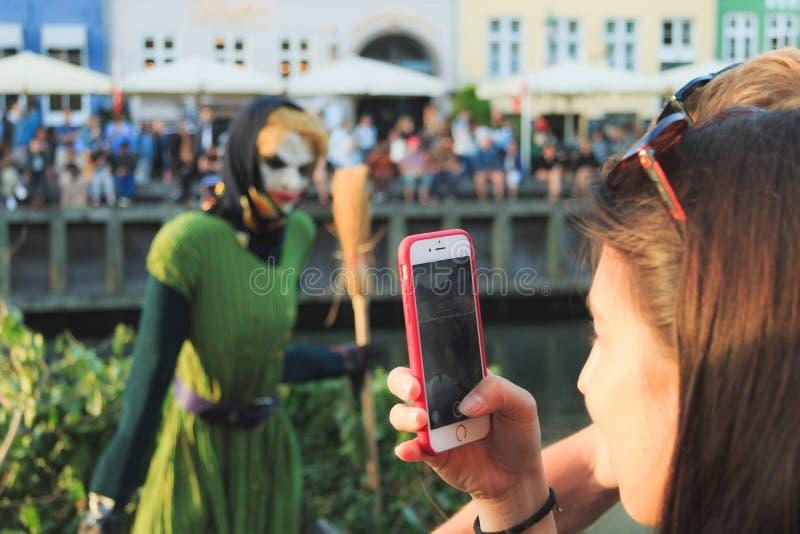 Девушка на Eve St. John в порте Nyhavn фотографировать что перед гореть вниз стоковые фото