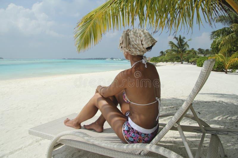 Девушка на lounger солнца под пальмой в мальдивском пляже стоковые фото