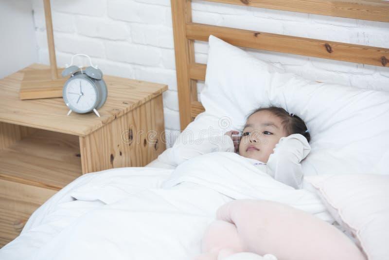 Девушка несчастного или плохого настроения азиатская кладет на уши крышки руки кровати от бодрствования утра вверх по часам стоковое фото
