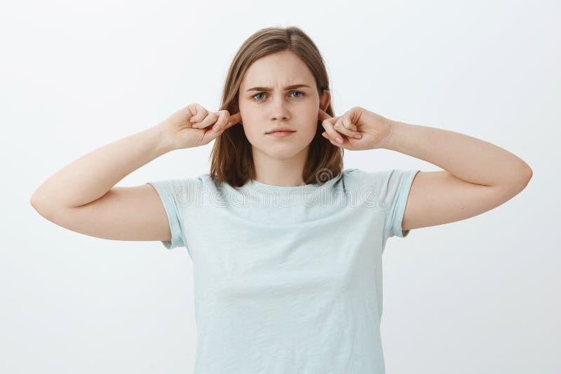 Девушка не идя слушает закрывающ вверх по ушам Интенсивный выглядящий серьезн докучанный слух заволакивания женщины с указательны стоковое фото