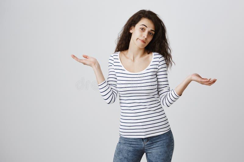 Девушка не имеет ничего добавить, был незнающая и равнодушна Привлекательная курчавая женственная женщина в вскользь обмундирован стоковое фото