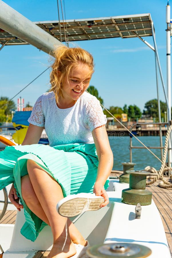 Девушка носит ботинки на палубе яхты смотря вокруг стоковое фото rf