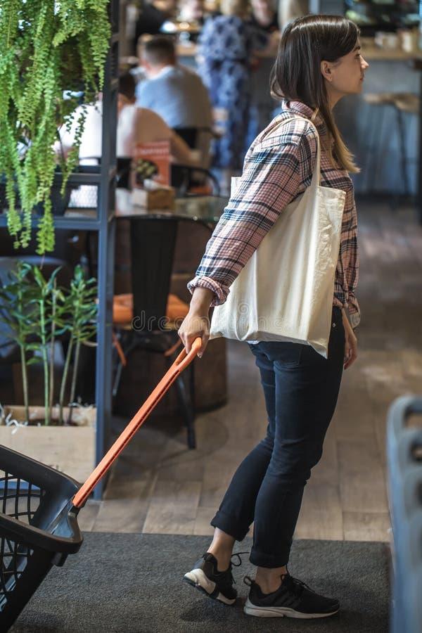девушка носит тележку в магазине и несет эко-мешок стоковое изображение