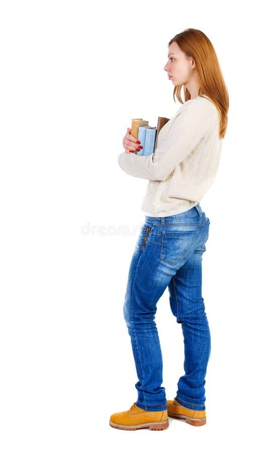 Девушка носит тяжелую кучу книг задний взгляд стоковое фото