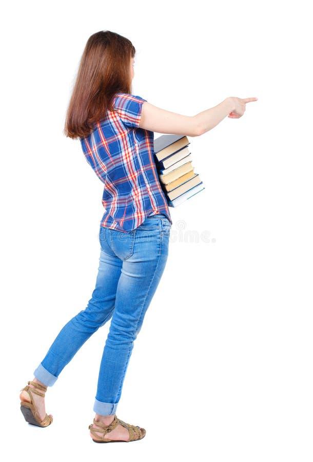 Девушка носит тяжелую кучу книг задний взгляд стоковое изображение rf