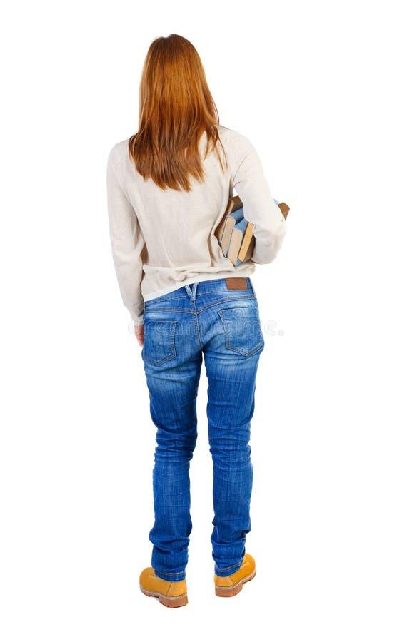 Девушка носит тяжелую кучу книг задний взгляд стоковые фото
