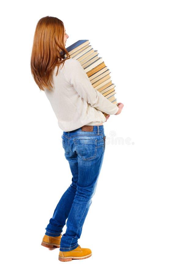 Девушка носит тяжелую кучу книг задний взгляд стоковое изображение