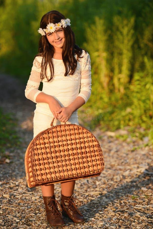 Девушка нося винтажную корзину пикника стоковое изображение rf