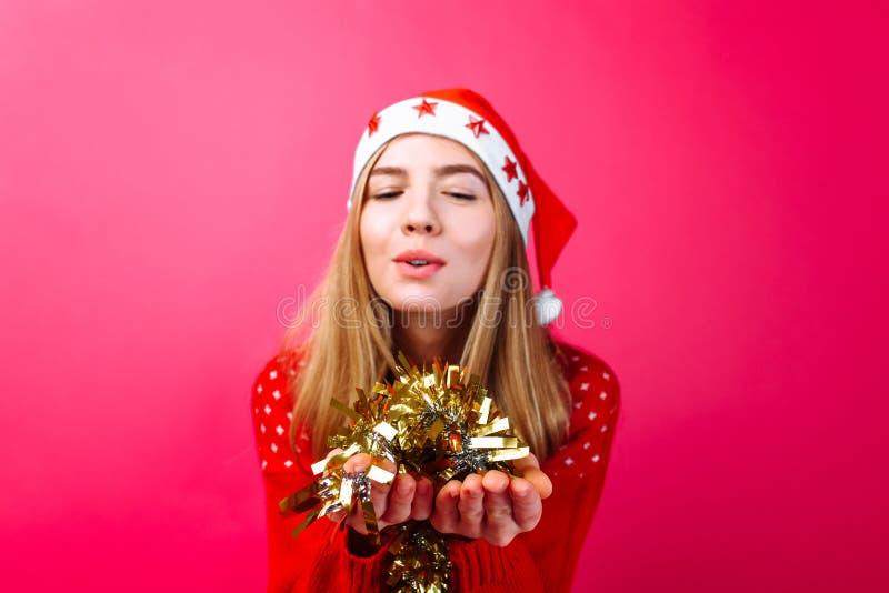Девушка нося красный свитер и шляпу Санта держит сусаль в ее руке и дуновения на ей, на красной предпосылке стоковые фото