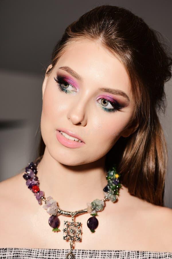Девушка нося красочный состав и ожерелье с любознательным взглядом стоковое фото rf