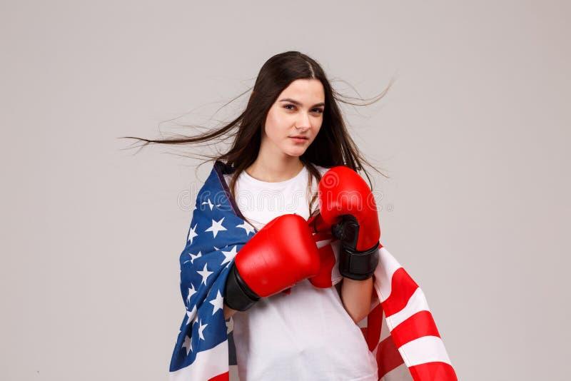 Девушка, нося перчатки бокса и покрытый с американским флагом стоковое фото rf