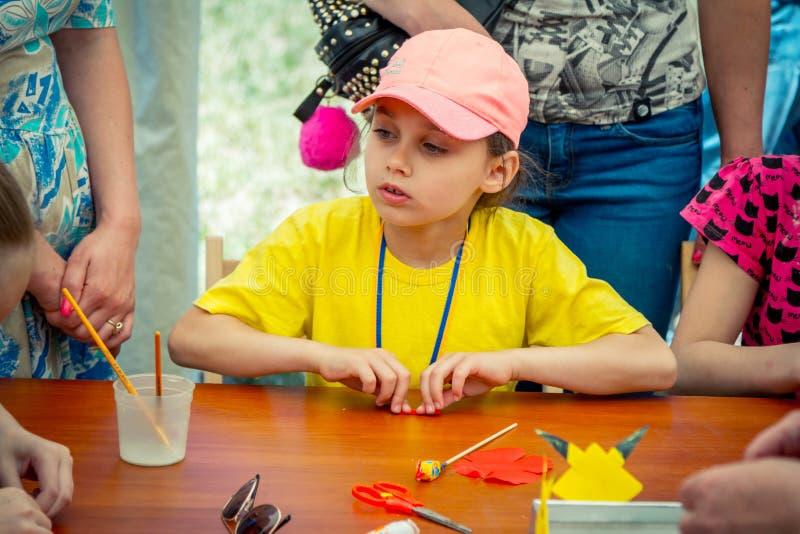Девушка, нося розовая крышка участвуя на искусстве и мастерская outdoors ремесла стоковые фотографии rf