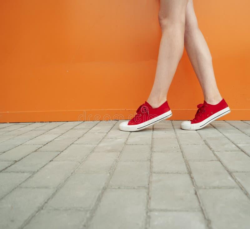 Девушка нося ультрамодные красные ботинки Ботинки закрывают вверх по всходу перед оранжевой стеной для магазина моды стоковая фотография rf