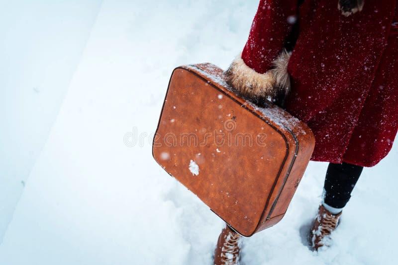 Девушка нося чемодан в снеге стоковые изображения