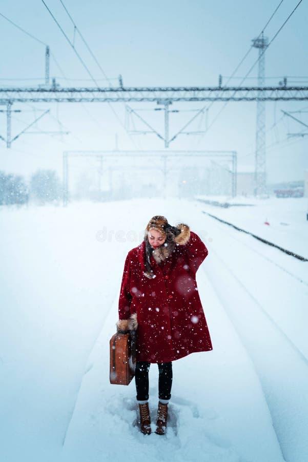 Девушка нося чемодан в снеге стоковое фото