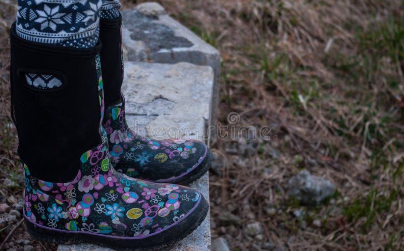 Девушка нося черные резиновые ботинки с розовыми дизайнами стоковые изображения rf