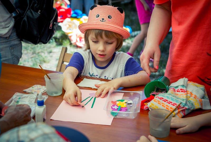 девушка, нося шляпа смешного кота форменная, участвующ на искусстве и мастерской outdoors ремесла стоковые фото